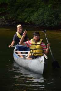 two boys posing in a canoe