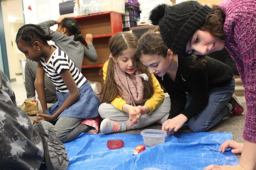 two girls working with each on a science experiment
