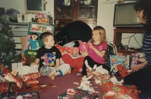 Lee and her younger brother open presents from their Christmas Sharing sponsor.