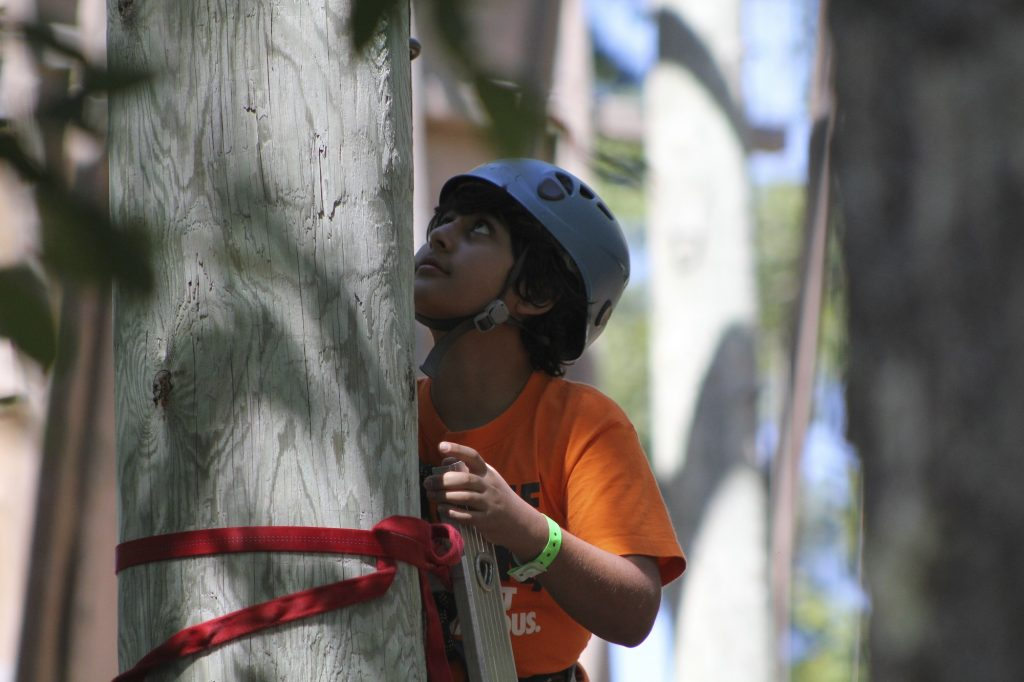 Boy reaches his goal on the high ropes